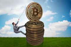 The businessman climbing the stack of bitcoins. Businessman climbing the stack of bitcoins Royalty Free Stock Photo