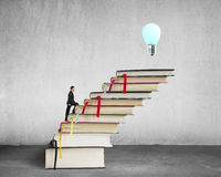 Businessman climbing on stack of books with growing bulb, buildi Royalty Free Stock Photo
