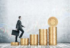 Businessman climbing stacks of bitcoins. Side view of a businessman climbing stacks of bitcoins in a concrete room with graphs drawn on a wall. Mock up Royalty Free Stock Image
