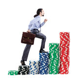 Businessman climbing stacks of  chips Royalty Free Stock Photo