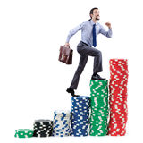 Businessman climbing stacks of chips Royalty Free Stock Photos