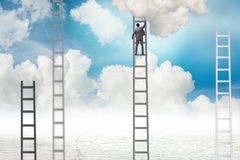The businessman climbing stairs against the sky Stock Photo