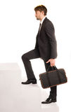 Businessman climbing stairs with a briefcase Royalty Free Stock Photos