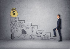 Businessman climbing stairs with economic charts Royalty Free Stock Photos