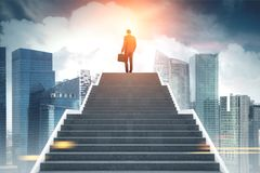 Businessman climbing stairs, morning city Stock Image
