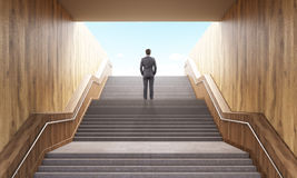 Businessman climbing stairs. Success concept. Business man climbing stairs leading to success in business. Successful man standing on top of career stairs. 3D Stock Photography
