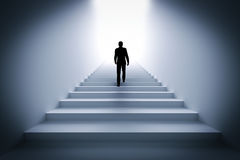 Businessman climbing the stairs towards light. Royalty Free Stock Photography