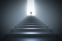 Businessman climbing the stairs towards light. Royalty Free Stock Images