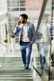 Businessman climbing stairs and using mobile phone in the Royalty Free Stock Images