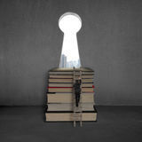 Businessman climbing to top of books with key shape door Royalty Free Stock Images
