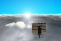 Businessman climbing to top of books, sun and cloudy below Stock Photo