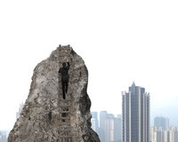 Businessman climbing to top of rocky mountain with city backgrou Royalty Free Stock Images