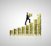 Businessman climbing up. On chart of gold coins Royalty Free Stock Photos