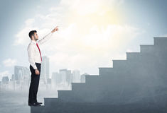 Businessman climbing up a concrete staircase concept Stock Photography