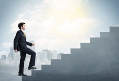 Businessman climbing up a concrete staircase concept Stock Images
