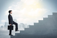 Businessman climbing up a concrete staircase concept Royalty Free Stock Photo