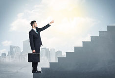 Businessman climbing up a concrete staircase concept Stock Photography
