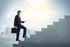 Businessman climbing up a concrete staircase concept Stock Image