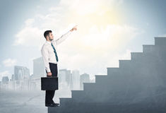 Businessman climbing up a concrete staircase concept. On city background Royalty Free Stock Images