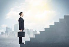 Businessman climbing up a concrete staircase concept Stock Image