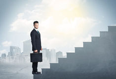 Businessman climbing up a concrete staircase concept Royalty Free Stock Images