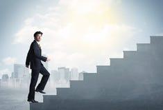 Businessman climbing up a concrete staircase concept Stock Photos