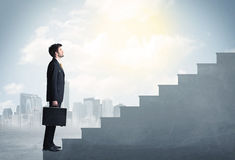 Businessman climbing up a concrete staircase concept Royalty Free Stock Photography