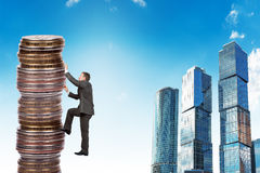 Businessman climbing up a huge stack of coins Stock Images