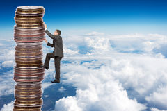 Businessman climbing up a huge stack of coins Stock Photo