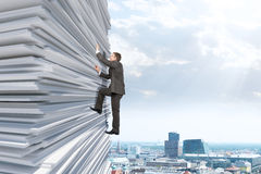 Businessman climbing up a huge stack of paper Stock Photography
