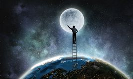 Businessman on ladder. Businessman climbing up the staircase as success achievement concept. Elements of this image are furnished by NASA Royalty Free Stock Photo