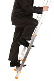 Businessman climbing upwards upon ladder. Close-up Royalty Free Stock Image