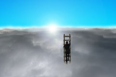 Businessman climbing wooden ladder through cloudy sky Stock Images
