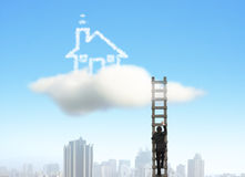 Businessman climbing on wooden ladder to cloud house, city under Stock Photography