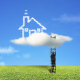 Businessman climbing on wooden ladder to reach cloud house Royalty Free Stock Image