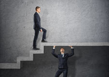 Businessman climbs the concrete stairs, which the other person keeps. Stock Image