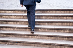 Businessman climbs a flight of stairs. A businessman climbs a flight of stairs Royalty Free Stock Photo