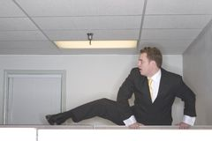Businessman climbs over cubicl stock image