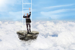 Businessman climbs stairs above clouds Stock Photo