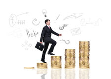 Businessman climbs up on the gold coins Royalty Free Stock Photography
