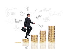 Businessman climbs up on the gold coins Stock Images