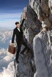 Businessman Clinging Onto Rock Stock Images