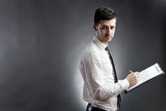 Businessman with clipboard. Unhappy businessman writing resignation letter on clipboard, dark studio background royalty free stock images