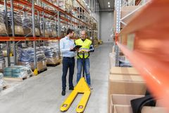 Businessman with clipboard and loader at warehouse. Logistic business, shipment and people concept - businessman with clipboard and warehouse worker with loader Royalty Free Stock Photography