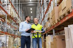 Businessman with clipboard and loader at warehouse. Logistic business, shipment and people concept - businessman with clipboard and warehouse worker with loader Stock Image