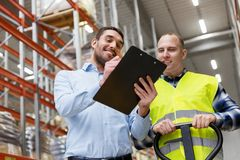 Businessman with clipboard and loader at warehouse. Logistic business, shipment and people concept - businessman with clipboard and warehouse worker with loader Stock Photos