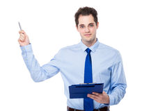 Businessman with clipboard and pen point up Stock Photo
