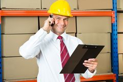 Businessman With Clipboard Using Mobile Phone Royalty Free Stock Photography