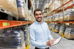 Businessman with clipboard at warehouse. Logistic business, shipment and people concept - happy businessman with clipboard at warehouse Stock Images