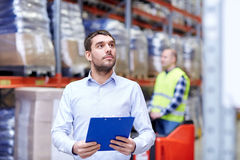 Businessman with clipboard at warehouse Stock Image